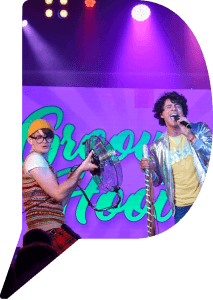 Andy and the Odd Socks performing on stage. Andy is wearing a silver jacket and singing, while another band member holds up a large floor fan.