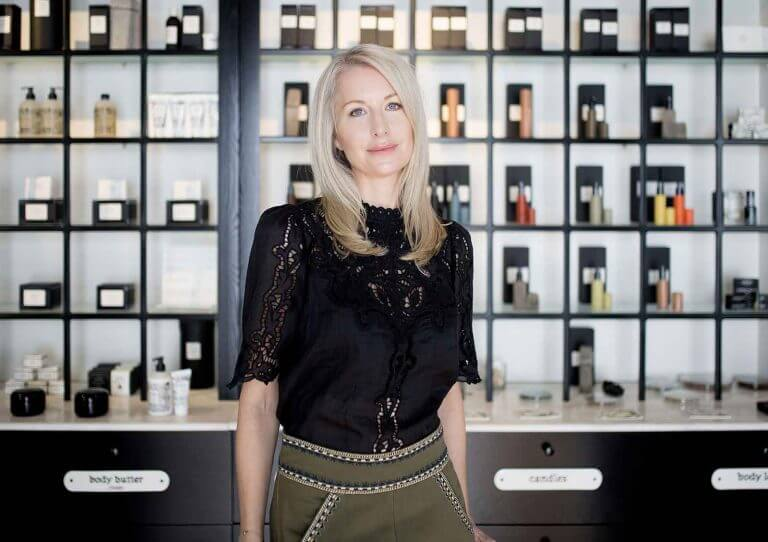 Kelly Alder, author, stood in front of a cabinet containing cosmetic products.